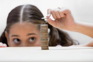 Girl placing a coin on stack
