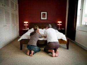 Mature couple kneeling by bed, praying, rear view